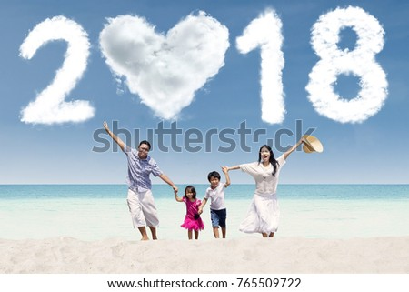Cheerful parents running with their children under clouds shaped numbers 2018 and heart. Shot in the beach