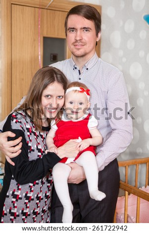 Cheerful parents with their little daughter in bedroom - stock photo