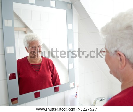 cheerful pensioner looking in the mirror - stock photo