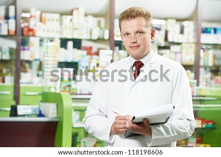 cheerful pharmacist chemist man standing in pharmacy drugstore - stock photo