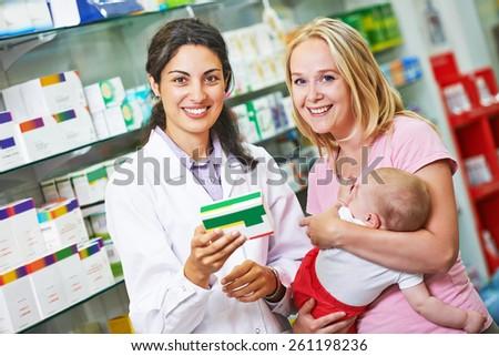 Cheerful pharmacist chemist woman giving vitamins to child girl in pharmacy drugstore - stock photo