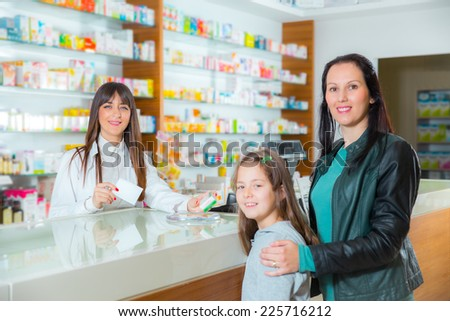Cheerful pharmacist chemist woman giving vitamins to child girl in pharmacy drugstore, selective focus
