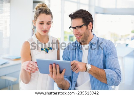 Cheerful photo editors working together on tablet pc in office - stock photo