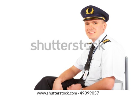 Cheerful pilot wearing uniform with epaulets and hat with golden wings, sitting, isolated on white background. - stock photo