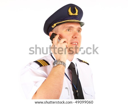 Cheerful pilot wearing uniform with epaulets and hat with golden wings, talking on mobile phone, standing isolated on white background.