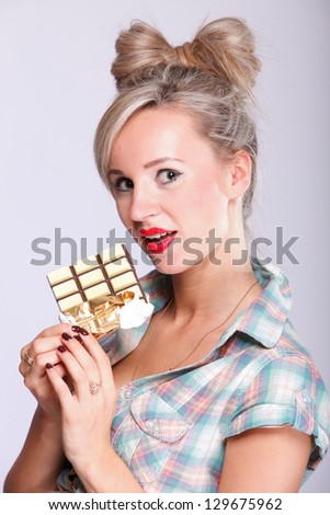 Cheerful pin up girl retro style portrait pinup Woman eating chocolate pink background