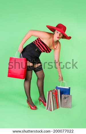Cheerful pinup girl holding shopping bags - stock photo