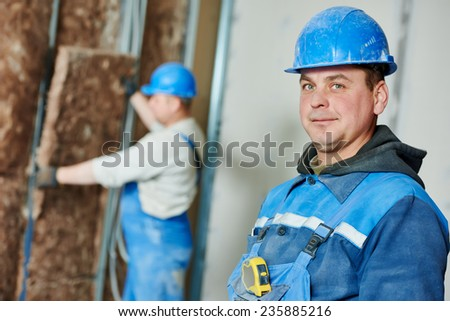 cheerful plasterer worker at a indoors wall insulation works - stock photo