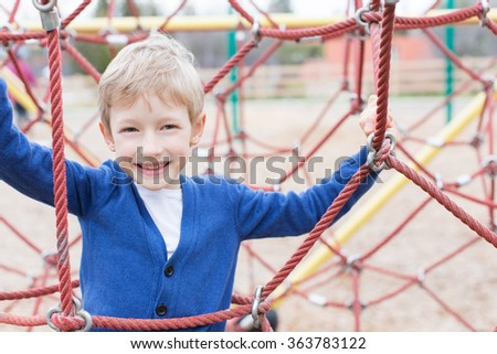 cheerful positive boy enjoying fun time at the playground - stock photo