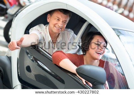 Cheerful positive charming adult couple sitting in electric car on city street  - stock photo