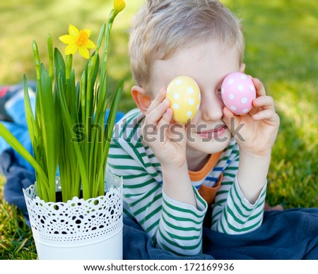 cheerful positive little boy holding colorful eggs at easter time - stock photo