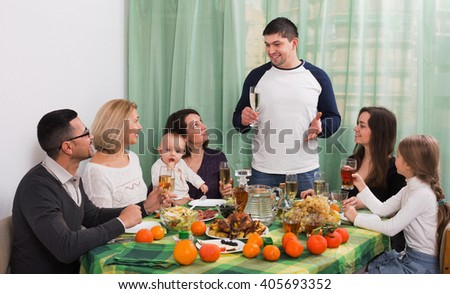 Cheerful positive multigenerational family sitting at holiday table, toasting and smiling - stock photo