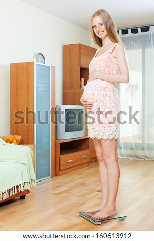 Cheerful pregnancy woman weighing herself on bathroom scale