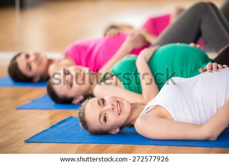 Cheerful pregnant women in yoga class are lying on mats in a fitness studio. - stock photo