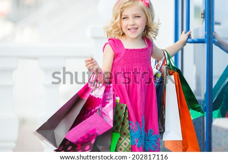 Cheerful preschool girl walking with shopping bags. Pretty smiling little girl with shopping bags with thumb up sign in the shop - stock photo
