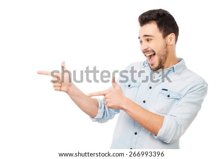 Cheerful presenter on your advertisement. Handsome young man in shirt pointing away while standing against white background - stock photo