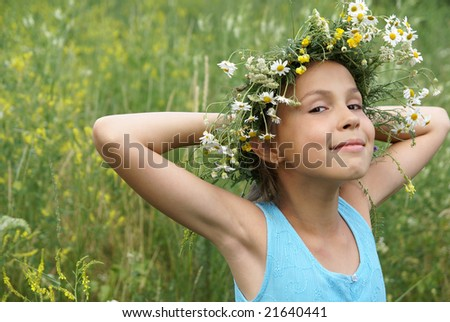 Cheerful preteen girl in field flower garland on green grass background - stock photo
