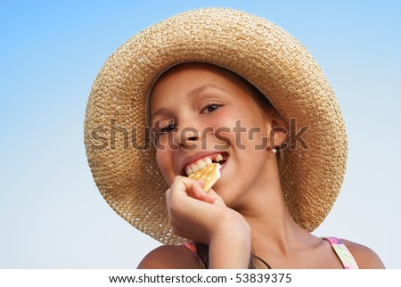 Cheerful preteen girl in straw hat eating cookie on blue sky background