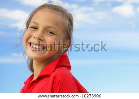 Cheerful preteen girl on blue sky background - stock photo