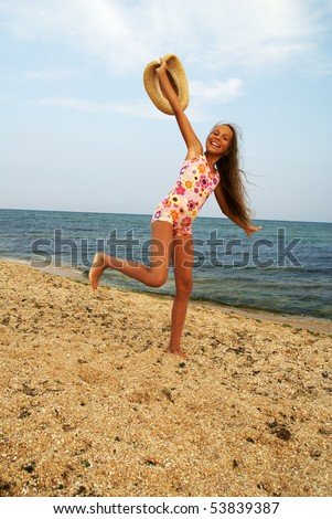 Cheerful preteen girl with straw hat running on sea beach - stock photo