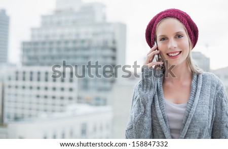 Cheerful pretty blonde on the phone outdoors on urban background - stock photo