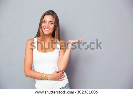Cheerful pretty girl holding copyspace on the palm over gray background - stock photo