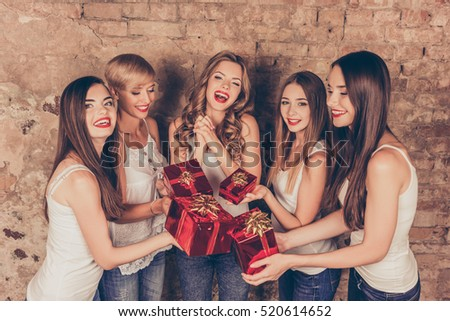 Cheerful pretty girls giving presents to their friend.