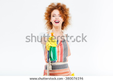 Cheerful pretty redhead young woman in striped apron and yellow gloves holding spray with liquid detergent over white background - stock photo