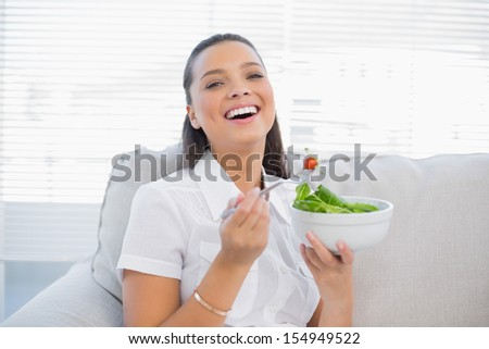 Cheerful pretty woman holding healthy salad sitting on sofa in bright living room