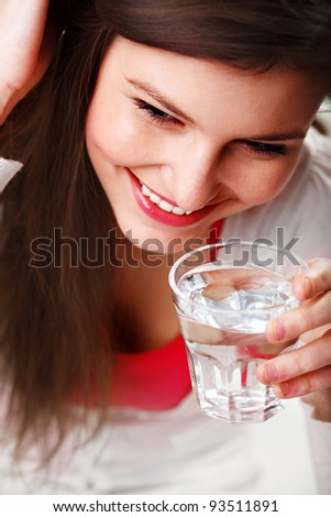 Cheerful pretty young girl holding a glass of water against white background