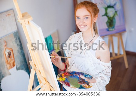 Cheerful pretty young woman artist standing and painting picture in artist workshop - stock photo