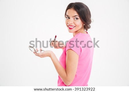 Cheerful pretty young woman holding mirror and applying lipstick over white background - stock photo