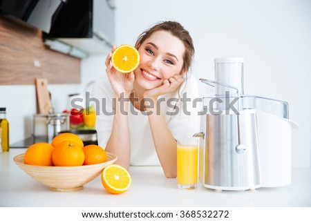 Cheerful pretty young woman showing half of orange sitting on the kitchen - stock photo