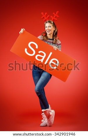 Cheerful pretty young woman wearing Christmas deer horns holding sale board. Beauty, fashion. Shopping. Full length portrait. - stock photo