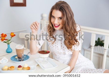 Cheerful pretty young woman with beautiful curly hair eating dessert and drinking latte in cafe  - stock photo