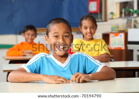 Cheerful primary school children in classroom - stock photo