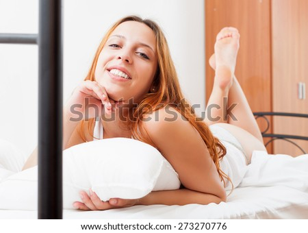 Cheerful red-haired woman waking up happily on white sheets on her bed at home  - stock photo