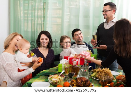 Cheerful relatives wishing little girl happy birthday and giving presents - stock photo