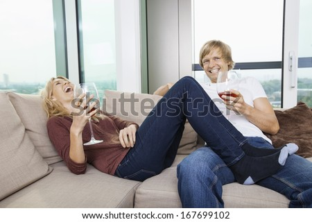 Cheerful relaxed couple with wine glasses in living room at home - stock photo