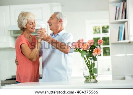 Cheerful retired couple dancing in kitchen - stock photo