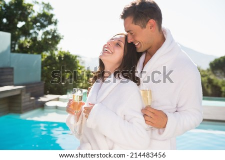 Cheerful romantic young couple with champagne flutes by swimming pool - stock photo