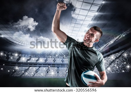 Cheerful rugby player punching the air against football stadium with fans in white - stock photo