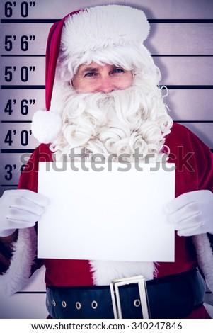 Cheerful santa claus holding page against mug shot background - stock photo