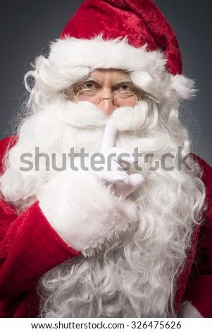 Cheerful santa claus showing a silence sign - stock photo