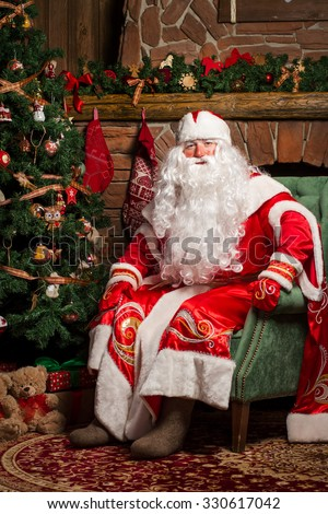 Cheerful Santa Claus sitting at his chair with fireplace and Christmas Tree in the background  - stock photo