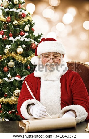 cheerful Santa Claus writing on scroll paper with quill - stock photo