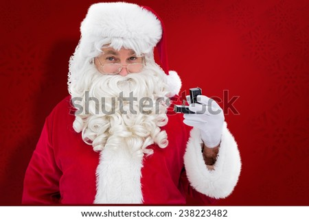 Cheerful santa holding a jewelry box against red snowflake background