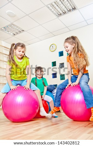 Cheerful school students hopping on gym balls - stock photo