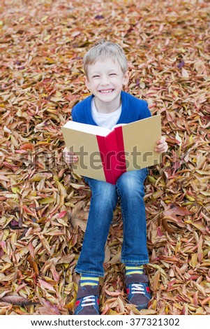 cheerful schoolboy holding book and ready for school sitting in yellow autumn leaves - stock photo