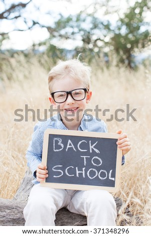 cheerful schoolboy in glasses holding blackboard with back to school sign, back to school concept - stock photo